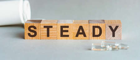 STABLE is a word written in black letters on wooden cubes, gray bsckground.