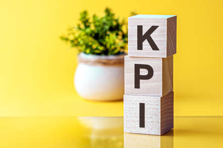 KPI - conceptual text on wooden cubes on a bright yellow background and a pot with a flower behind. the letters in black
