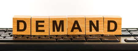 DEMAND word made with building blocks. A row of wooden cubes with a word written in black font is located on a black keyboard.