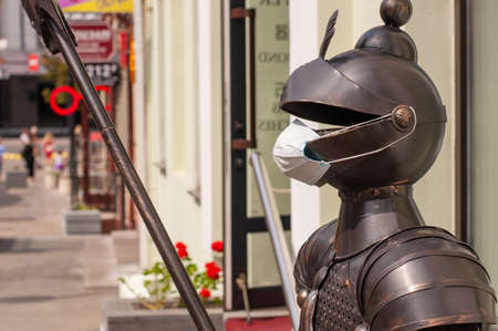 armor of a knight with a medical mask during quarantine at the entrance to a restaurant. Stock fotó