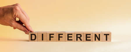 DIFFERENT message word on a wooden desk on cube blocks. The hand puts a wooden cube with the letter D from the word DIFFERENT. The word is written on cubes standing on the yellow surface of the table.