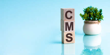 Acronym CMS - content management system. Wooden small cubes with letters isolated on yellow background. Business Concept image.