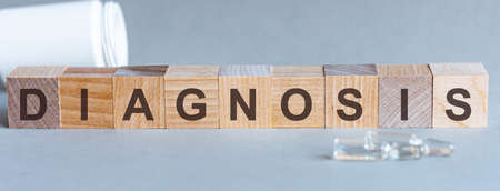 DIAGNOSIS - words from wooden blocks with letters, feel worried and nervous stress concept, top view light background.