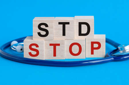 Wooden block with words Stop STD - Sexually transmitted diseases - with stethoscope on the table, insurance and medical concept, blue background