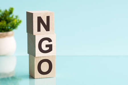 Word NGO - Non-governmental organization - on a wooden cubes on a blue background.
