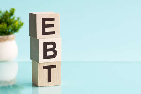 EBT - acronym from wooden blocks with letters, Earnings before interest, taxes, depreciation and amortization. Blue background.