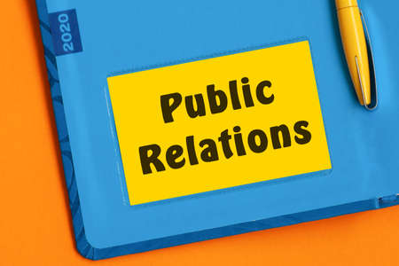 The words Public Relations is written in black marker on the yellow paper for notes. Concept
