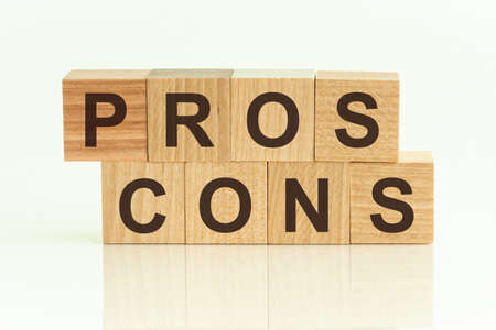 Pros Cons - text on wooden cubes on a gradient background