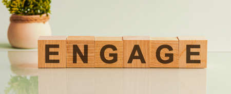 Engage word written on wood block. Engage motivation text on wooden blocks business concept white background. Front view concepts, flower in the background.