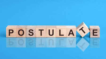 Text POSTULATE on wood cube block, stock investment concept. The text POSTULATE is written on the cubes in black letters, the cubes are located on a blue glass surface.