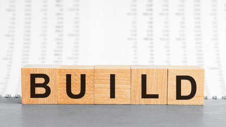 Build word made with building blocks. Build on wooden cubes on gray notepad. Business concept.