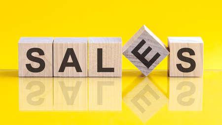 sales word written on wood block. sales word is made of wooden building blocks lying on the yellow table. sales, business concept, yellow background