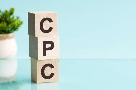 CPC - acronym from wooden blocks with letters, Cost Per Click, taxes, depreciation and amortization. Blue background. Foto de archivo