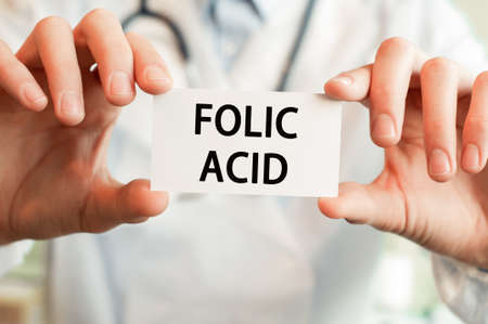 Doctor holding a card with text FOLIC ACID in both hands. Medical concept, Banque d'images