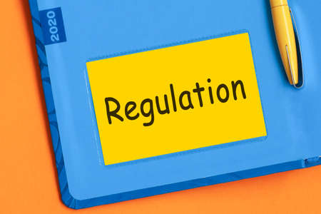 The words REGULATION is written in black letters on the yellow paper for notes