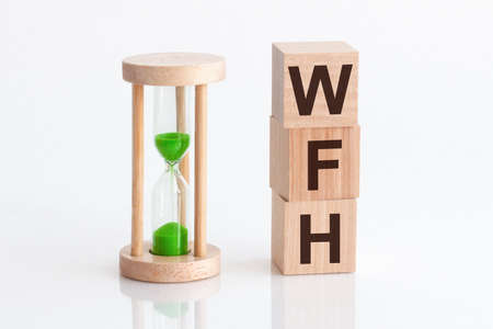 Close-up of an hourglass next to wooden blocks with the text WFH. WFH - Working from Home - text in wooden building blocks, white backgrounds. Banco de Imagens