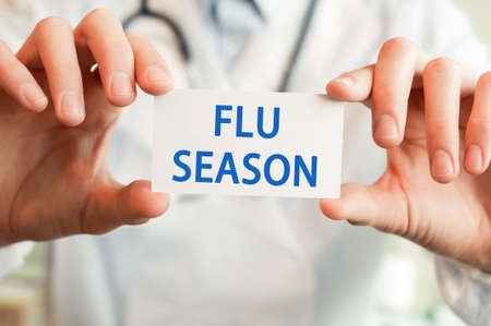 Doctor holding a card with text FLU SEASON in both hands. Medical concept,