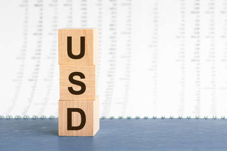 text usd on vertical row of wooden blocks on the background of columns of numbers. USD text on wooden cubes on blue backround. Business concept.