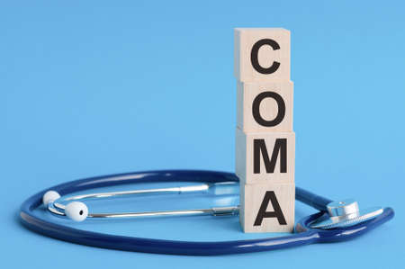 coma word written on wooden blocks and stethoscope on light blue background. insurance and medical concept