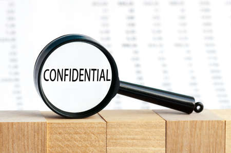 text CONFIDENTIAL, business concept image with soft focus background. Magnifying glass on the background of columns of numbers.