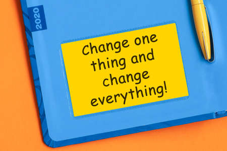 The words hange one thing and change everything is written in black letters on yellow note paper. A yellow pen is embedded in the background of the blue diary.