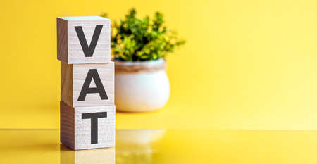 Motivational Words: VAT in 3d wooden alphabet letters on a bright yellow background with copy space. business concept Reklamní fotografie