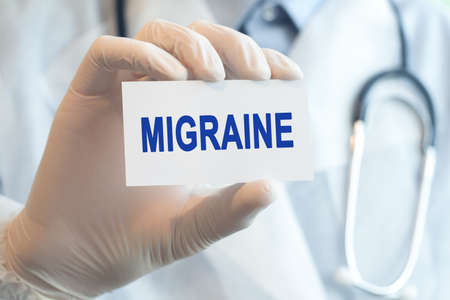 Doctor holding a paper card with text MIGRAINE, medical concept