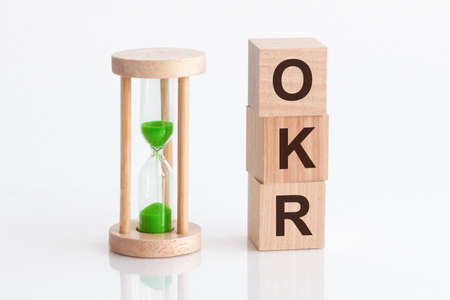 close-up of an hourglass next to wooden blocks with the text OKR. OKR - Objectives and Key Results.