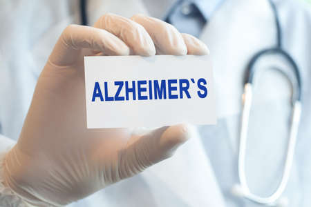 Doctor holding a white paper card with text ALZHEIMERS, medical concept. ALZHEIMERS card in hands of medical doctor