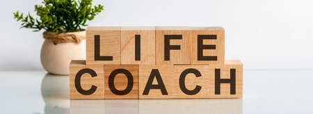 LIFE COACH motivation text on wooden blocks business concept white background. Front view concepts, flower in the background.