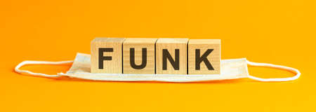funk the word is written on wooden cubes lying on a white medical face mask, yellow background, concept