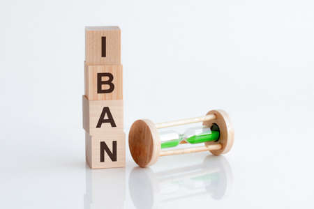 hourglass and wooden blocks with the word Iban, business concept. Making the right decision.