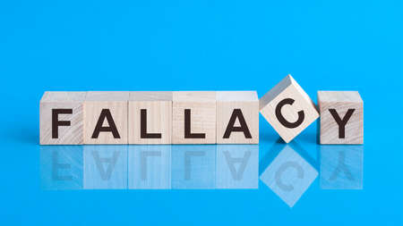 Text FALLACY on wood cube block, stock concept. The text FALLACY is written on the cubes in black letters, the cubes are located on a blue glass surface.