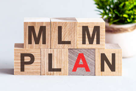 MLM PLAN word written on wood block. Faqs text on table, concept. MLM - Multilevel marketing