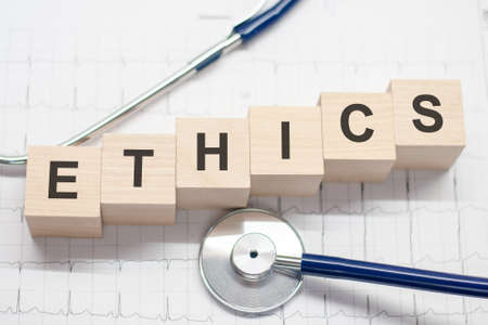 Ethics word written on wooden blocks and stethoscope on light background. Healthcare conceptual for hospital, clinic and medical busines.