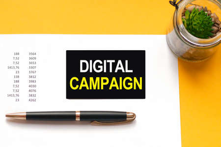 A black pen, a green plant in a glass jar, and a black card on a white sheet of paper on yellow background. Text: DIGITAL CAMPAIGN, white and yellow letters. Financial and motivation concept.