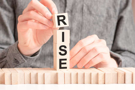 The hand puts a wooden cube with the letter R from the word RISE. The word is written on wooden cubes standing on the white surface of the table.