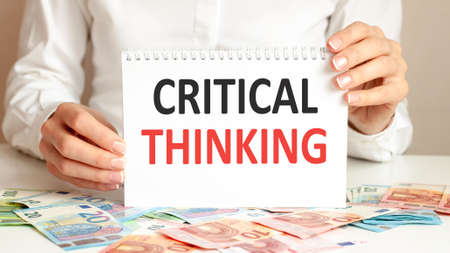 A woman in a white shirt holds a piece of paper with the text: CRITICAL THINKING. Business concept for companies and educational institutions. Banknotes and tablet on a table, background.