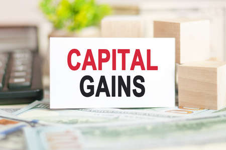 The word CAPITAL GAINS is written on white paper card near a wooden cubes, calculator on a banknotes background. Business and Financial concept