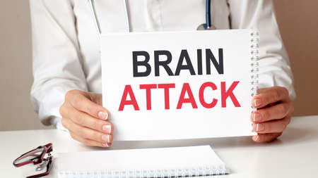 BRAIN ATTACK card in hands of medical Doctor. Doctor's hands a sheet of paper with text BRAIN ATTACK, medical concept.