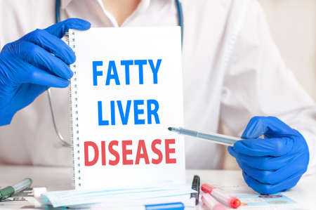 A sheet of paper with text FATTY LIVER DISEASE, stethoscope and medical documents on the table. Medical concept.