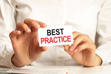 A woman in a white shirt holds a piece of paper with the text: BEST PRACTICE. Business concept for companies. Фото со стока