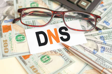 The letters DNS are written on a white card lying on the bills, glasses, pen and calculator in the background. DNS short for Domain Name System. Business and finance concept.