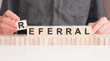 The hand puts a wooden cube with the letter R from the word Referral. The word is written on wooden cubes standing on the white surface of the table.