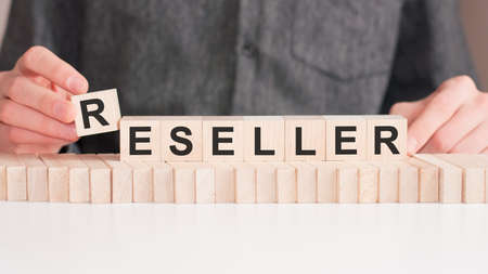 The hand puts a wooden cube with the letter R from the word RESELLER. The word is written on wooden cubes standing on the white surface of the table.
