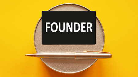 founder - words writing a white letters on a sheet paper. Black card with text on a yellow background with round metal stand and metal writing pen. Business, finance and education concept