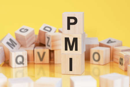 wooden cubes with letters pmi arranged in a vertical pyramid, yellow background, reflection from the surface of the table, business concept. pmi - short for project management institute