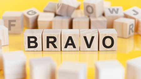 the word bravo is written on a wooden cubes structure. blocks on a bright background. financial concept. selective focus