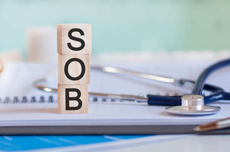 The word SOB is written on wooden cubes near a stethoscope on a paper background. SOB - short for shortness of breath. Medical concept.