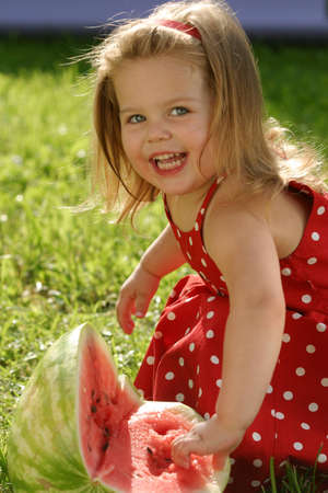 Little girl in red dress eating watermelon photo